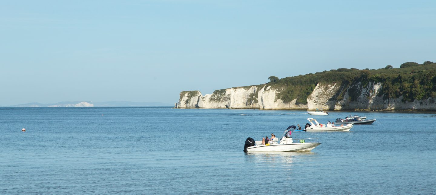 Studland Bay view with motor boats and white cliffs