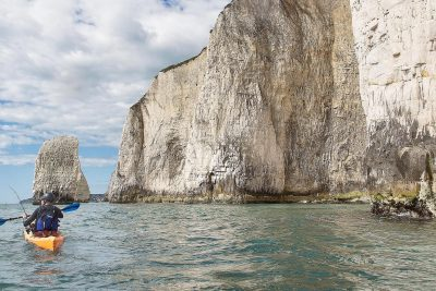 A man kayaks on the beneath chalk cliffs in Dorset.
