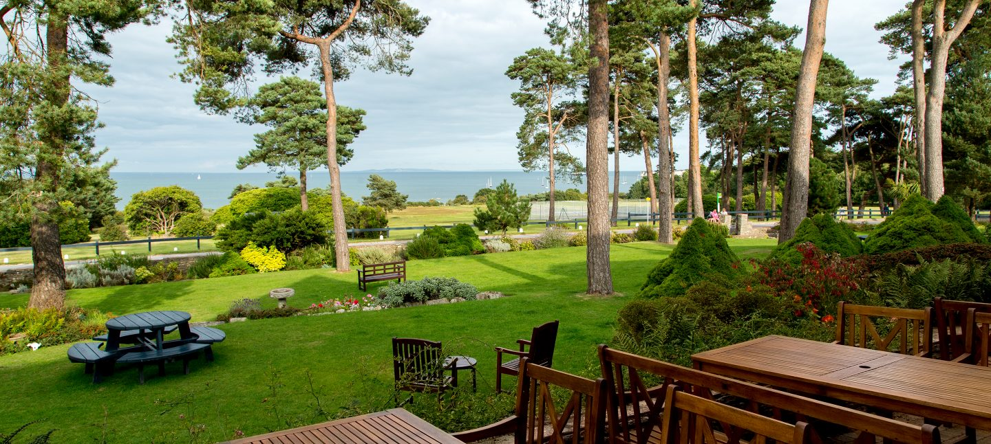 Trees and gardens overlooking the bay at a Dorset beach hotel
