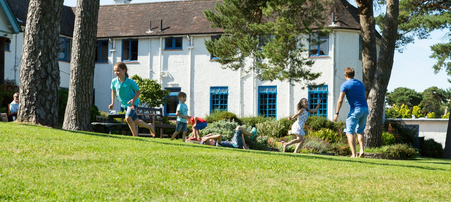 Children playing on the lawn enjoying a family holiday in Dorset