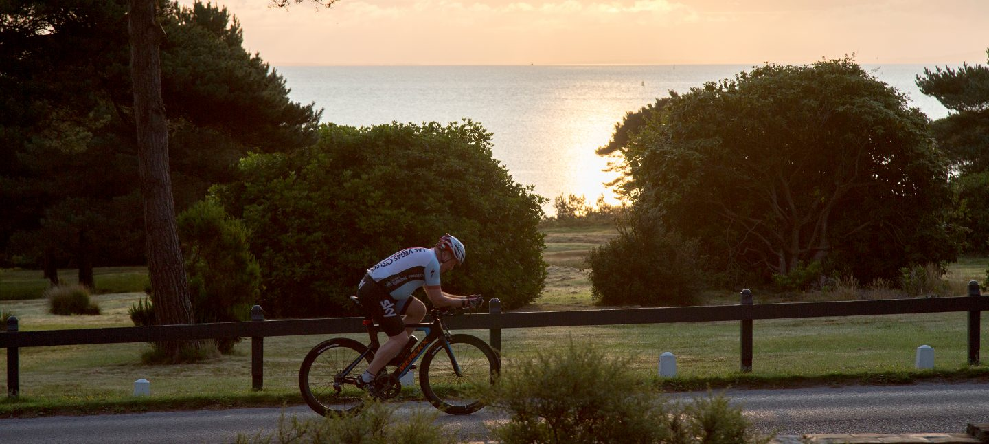 Cyclist travelling past the bay view of the Dorset beach hotel