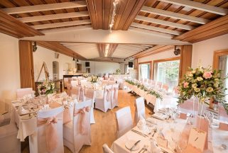 The Garden Room at Knoll House hotel, with tables set and decorations for a wedding dinner.