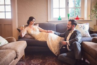 A newlywed couple drinks champagne in the Knoll House hotel lounge.