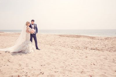 A newlywed couple standing on Studland Beach.